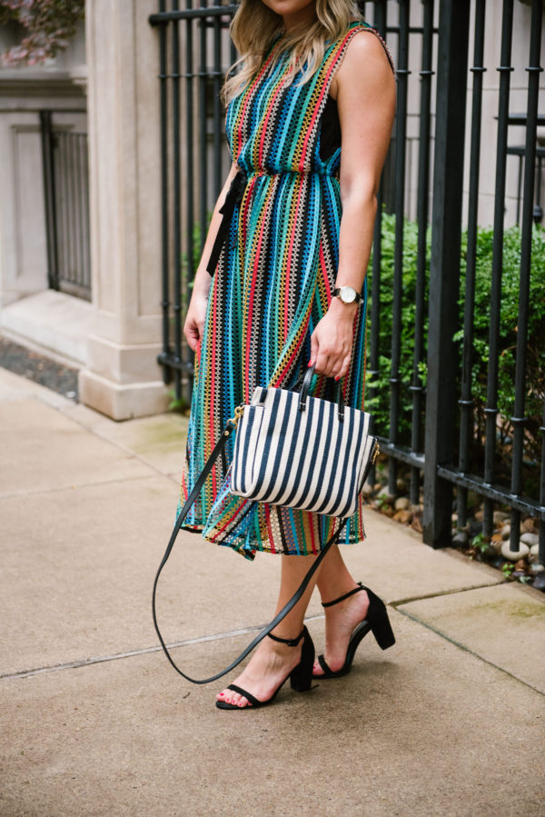 Bows & Sequins styling a rainbow crochet midi dress with a Clare V striped crossbody and black sandals.