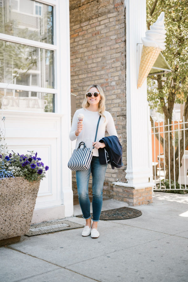 Bows & Sequins, a fashion-focused lifestyle blogger, wearing an Old Navy peplum tee, Kut from the Cloth skinny jeans, Sam Edelman woven leather loafers, and a Clare V striped canvas crossbody bag.