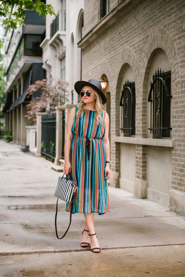 Travel blogger Bows & Sequins wearing a black straw hat, rainbow striped Eva Franco midi dress from Anthropologie, and black sandals.