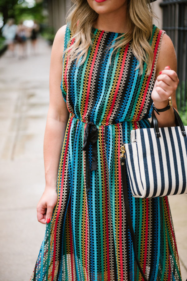 Chicago-based fashion blogger Bows & Sequins wearing an Eva Franco rainbow midi dress with a small striped bag.