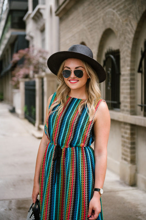 Fashion-focused lifestyle blogger Bows & Sequins wearing a rainbow striped sleeveless dress with a black straw hat and gold aviators.