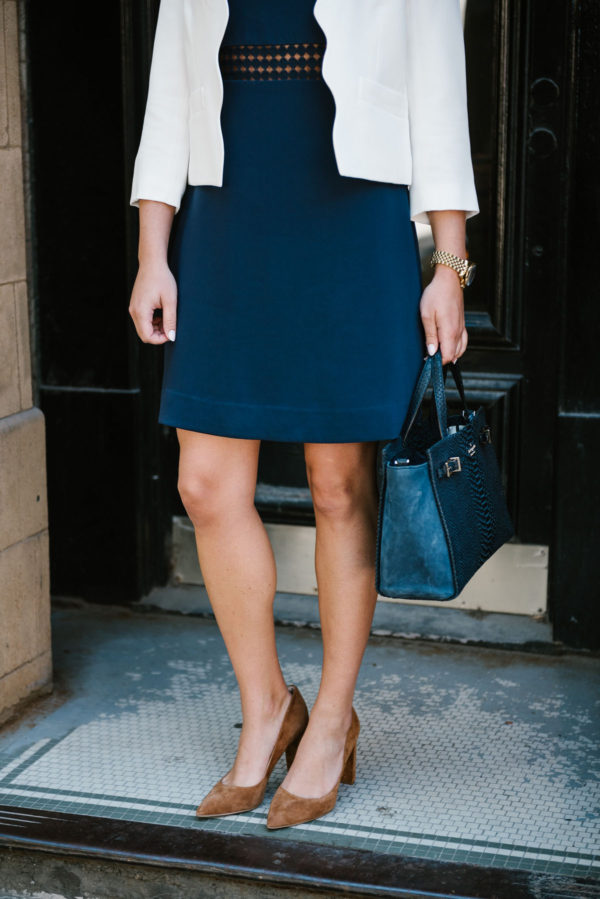 Bows & Sequins, a fashion-focused lifestyle blogger, wearing a navy dress, a white scalloped blazer, and brown suede pumps for work.
