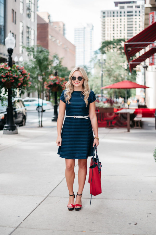Bows & Sequins styling a summer red, white, and blue outfit: a navy fit and flare dress with a white belt, a red Gigi x Tommy scarf tote, sunglasses, and red Tommy Hilfiger sandals.