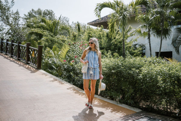 Jessica of Bows & Sequins, a Chicago-based fashion blog, styling a Vineyard Vines romper with a White Elephant Designs straw hat, a Clare V Petit Henri bucket bag and Soludos knotted slides.