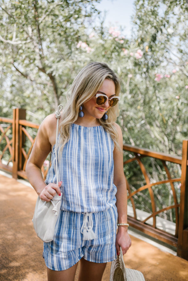 Bows & Sequins wearing white rim sunglasses, blue statement earrings, a blue and white striped romper, and a Clare V bucket bag.