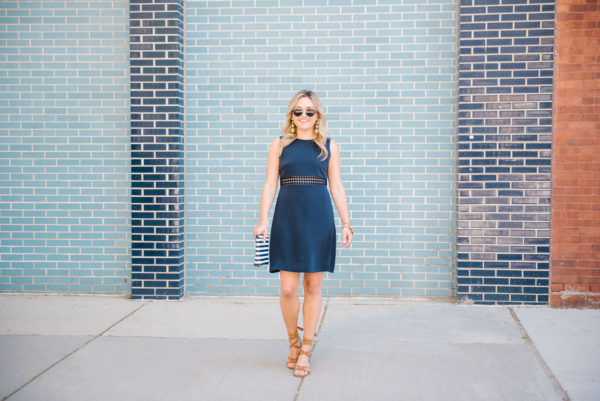 Bows & Sequins wearing a navy Sail to Sable dress with lace up block heel sandals in Chicago.