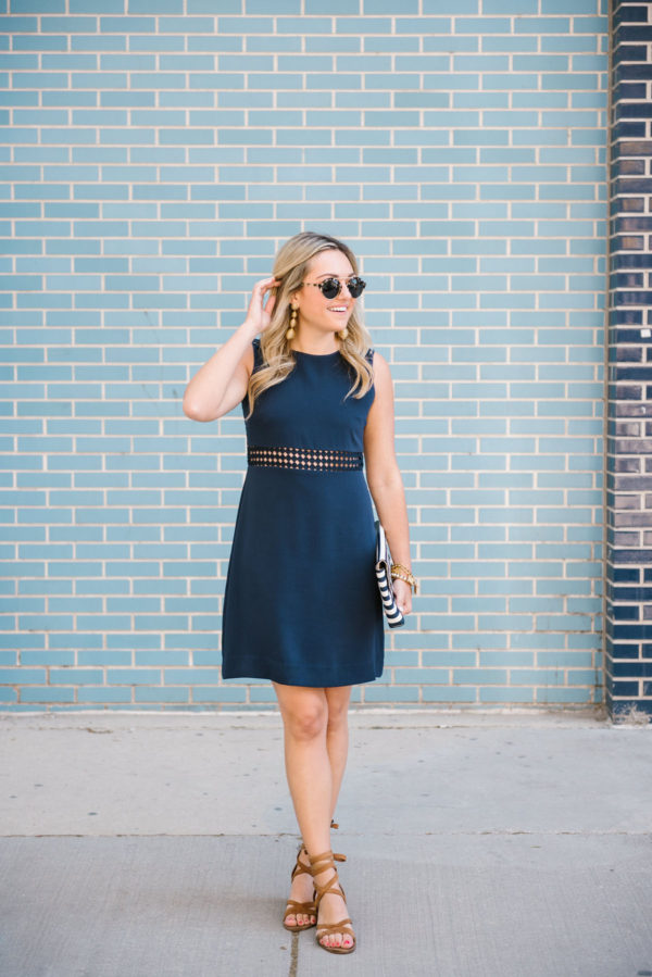 Jessica of Bows & Sequins, a Chicago-based fashion blog, wearing a navy Sail to Sable sleeveless dress with lace up sandals and Illesteva sunglasses.