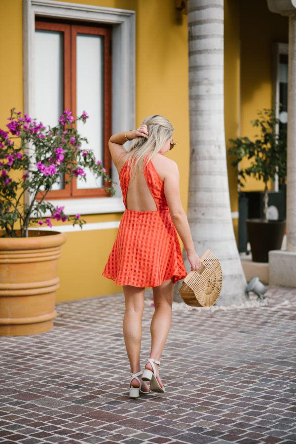Jessica of Bows & Sequins, a Chicago-based fashion blog, styling a backless Lovers + Friends orange dress with a Cult Gaia natural bamboo bag.