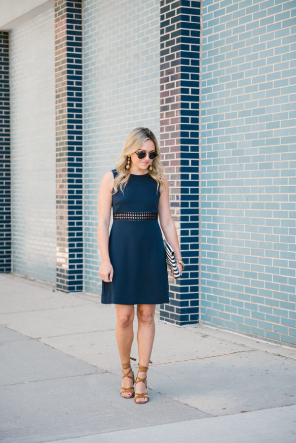 Bows & Sequins, a Chicago-based lifestyle blogger, wearing a sleeveless navy Sail to Sable dress for a wedding shower.