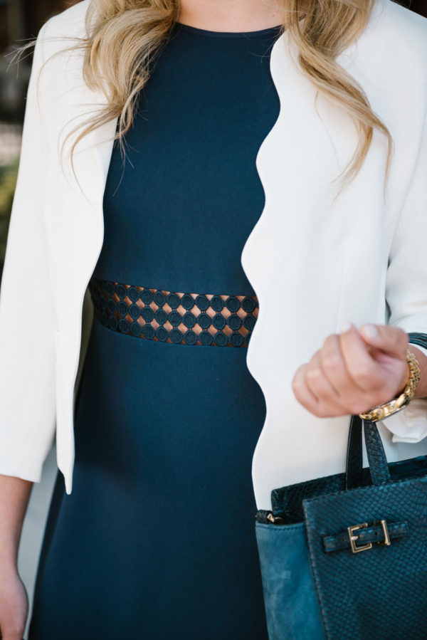 Bows & Sequins wearing a white scalloped blazer from Draper James with a navy Sail to Sable dot lace dress, and a Kate Spade navy bag.