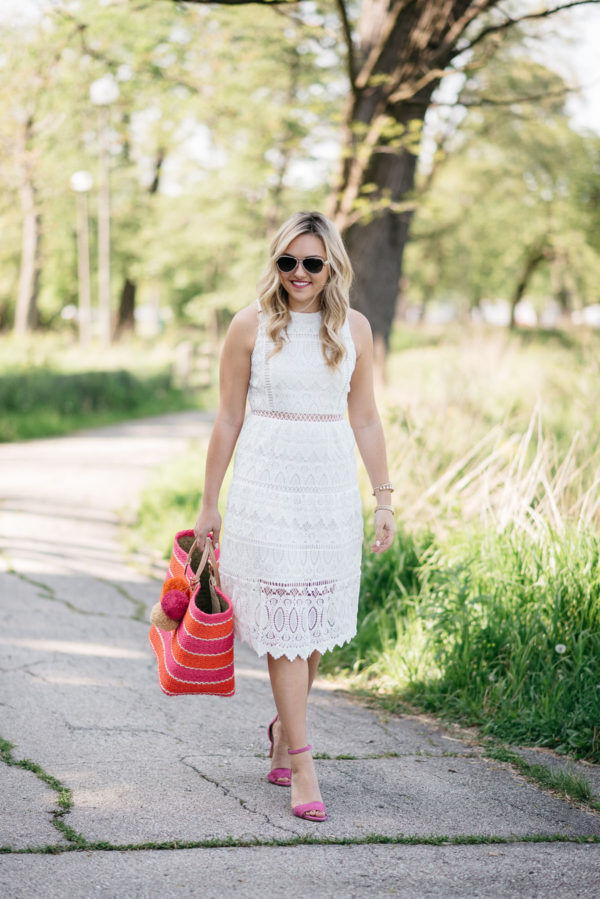 Bows & Sequins wearing a cut out white lace J.O.A. dress and pink heels, holding a pink and orange striped tote.
