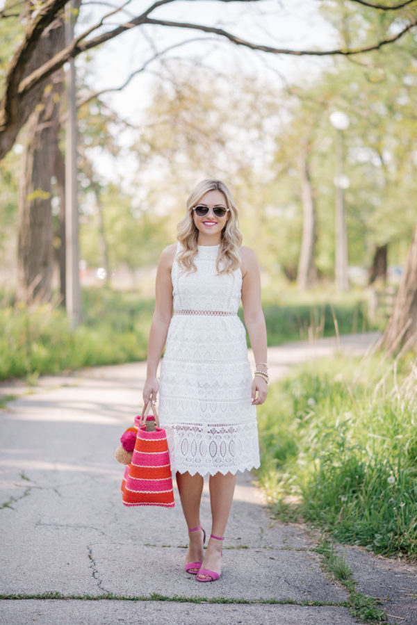 Jessica, of the Chicago-based fashion focused blog Bows & Sequins, wearing a J.O.A. white lace dress, aviators, and pink sandals, holding a pink and orange striped Mar y Sol straw tote.