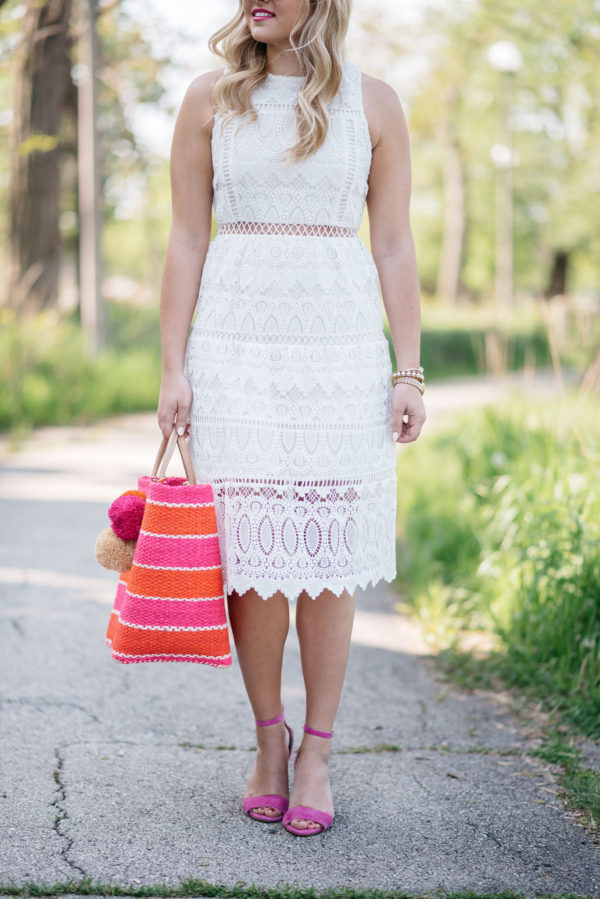 Chicago-based fashion blogger Bows & Sequins wearing a white lace dress for summer with a striped straw tote and pink strappy heels.