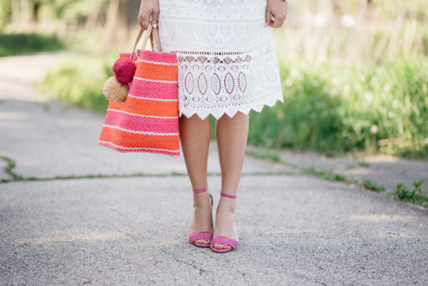 Bows & Sequins, a lifestyle Chicago blogger, wearing a white lace dress with pink sandals and a pink and orange striped tote.