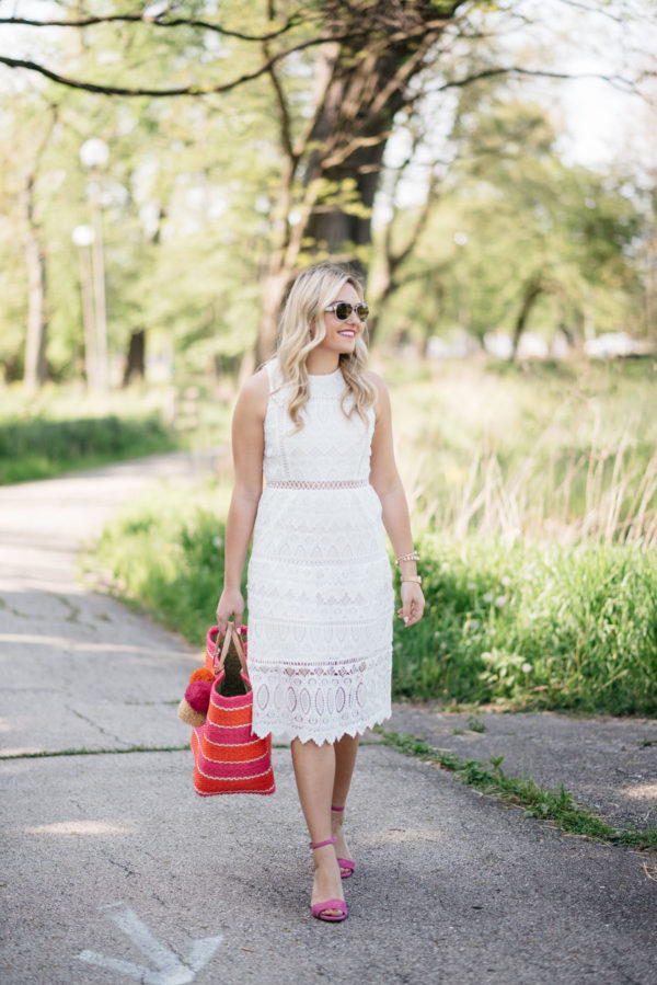 Bows & Sequins, a fashion-focused lifestyle blogger, wearing a J.O.A. white lace dress with a pink and orange striped tote and pink heels in a Chicago park