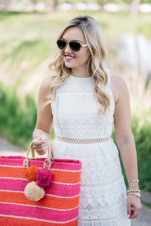 Bows & Sequins wearing a white lace dress and aviators and holding a pink and orange striped pom pom Mar y Sol tote.