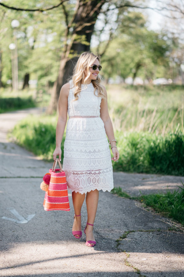 Chicago lifestyle blogger Bows & Sequins wearing a J.O.A. white lace dress and pink sandals and holding a pink and orange striped Mar y Sol straw tote.