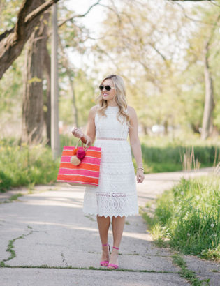 Chicago lifestyle blogger Bows & Sequins wearing a J.O.A. white lace dress and holding a pink and orange striped Mar y Sol straw tote.