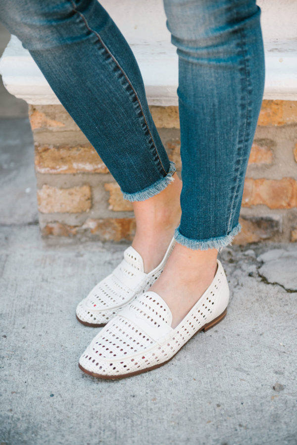 Bows & Sequins wearing raw hem skinny jeans and white Sam Edelman woven leather loafers.