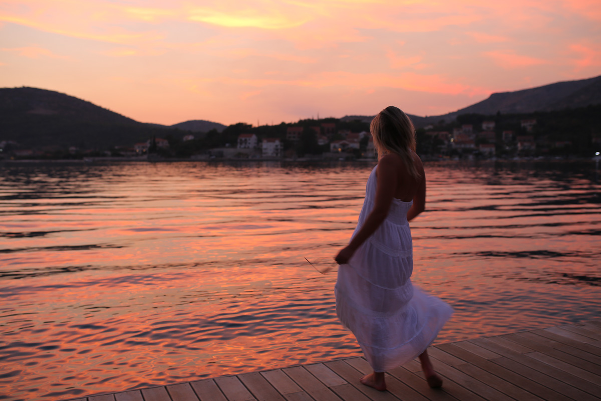 Travel blogger Bows & Sequins wearing a white maxi dress on a dock in Croatia at sunset.