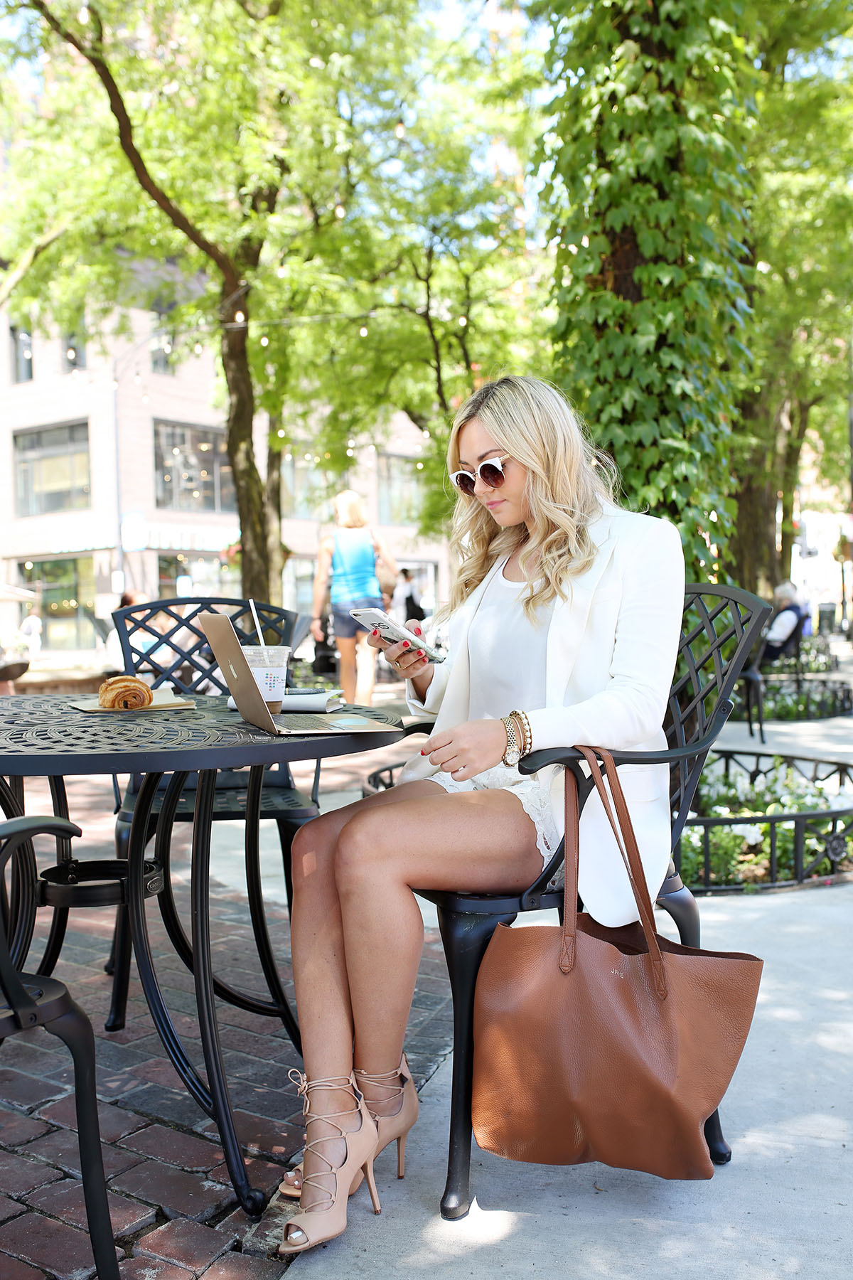 Bows & Sequins working outside in the Gold Coast in Chicago at Mariano Park wearing a white short suit and lace-up pumps.