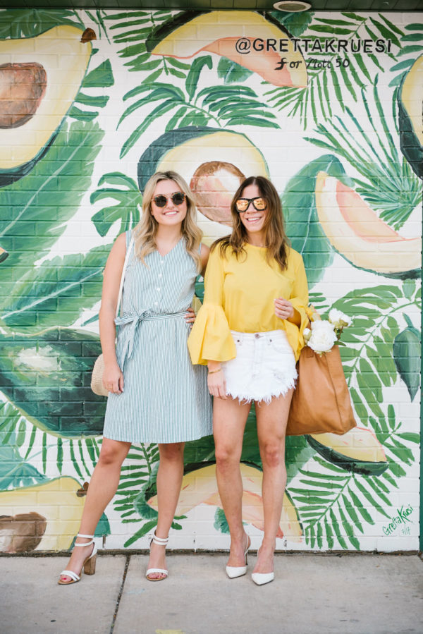 Jessica of Bows & Sequins and Hallie from Among Other Things standing in front of an avocado mural in Chicago.