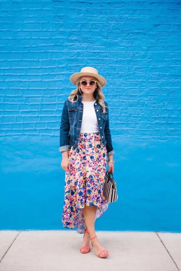 Fashion-focused lifestyle blogger Bows & Sequins wearing a Hutch floral high-low dress from Anthropologie with a denim jacket, Nordstrom sunglasses, and a L Space straw hat.