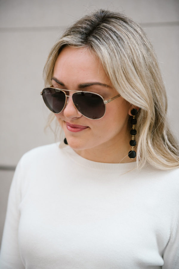 Bows & Sequins wearing a Halogen sweater, Gucci aviator sunglasses, and black drop Baublebar earrings.