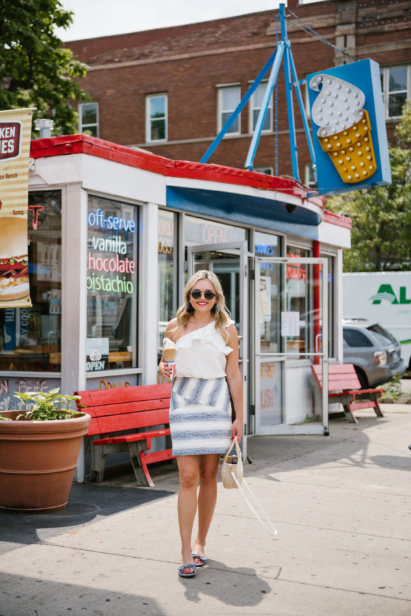 Bows & Sequins, a Chicago lifestyle blogger, wearing a one-shoulder white ruffle crop top with a blue striped Hutch mini skirt and J.Crew gingham bow slides.