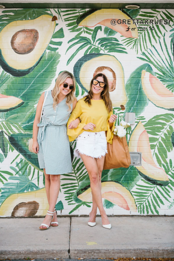 Chicago lifestyle bloggers Bows & Sequins and Among Other Things standing by an avocado art mural.