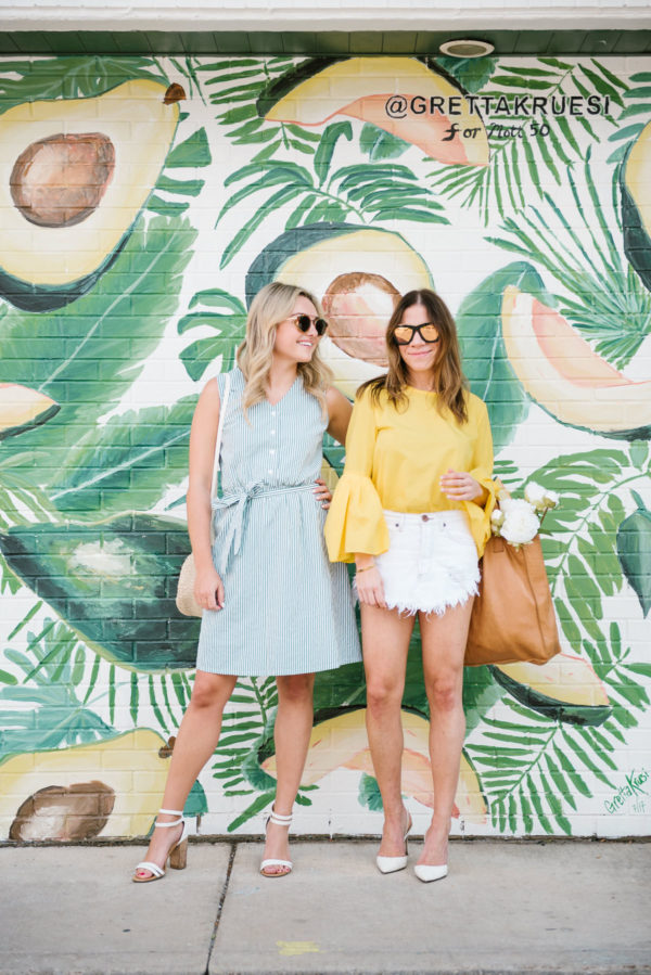 Fashion-focused lifestyle blogger Bows & Sequins wearing a striped midi dress with a Clare V straw bag and fitness blogger Among Other Things wearing a Zara top with a raw hem denim skirt and leather tote.