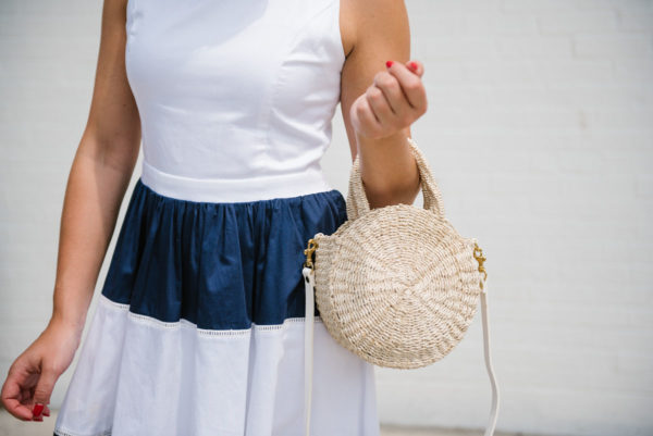 Chicago lifestyle blogger Bows & Sequins wearing a navy striped dress and holding a Clare V Petit Alice straw bag.