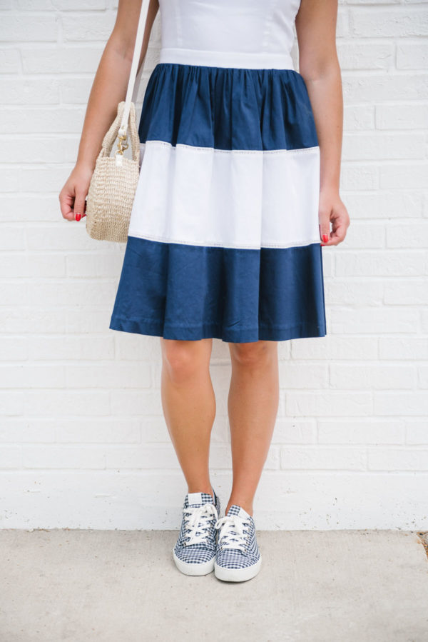 Bows & Sequins, a fashion-focused lifestyle blogger, wearing an Elizabeth McKay striped dress with Claudie Pierlot gingham sneakers.