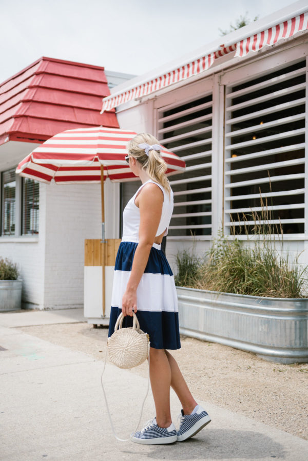 Bows & Sequins wearing a navy striped Elizabeth McKay dress with gingham sneakers and a J.Crew eyelet hair bow.