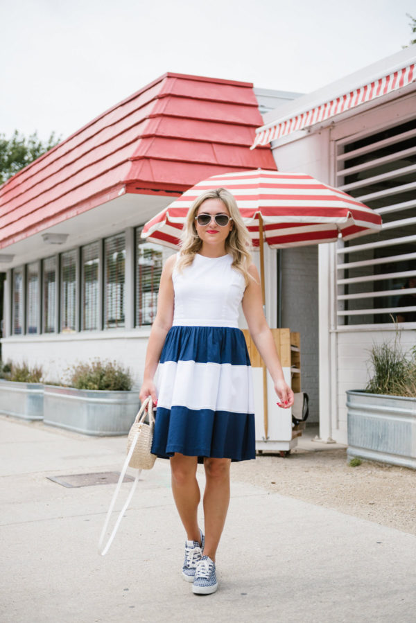 Bows & Sequins, a Chicago-based lifestyle blogger, wearing a navy and white striped dress with gingham sneakers, Coach aviators and a Clare V straw bag.