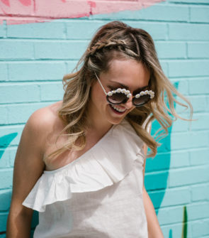 Bows & Sequins wearing a pair of daisy sunglasses and a ruffled one shoulder top with a hair braid for a music festival like Coachella or Lollapalooza.