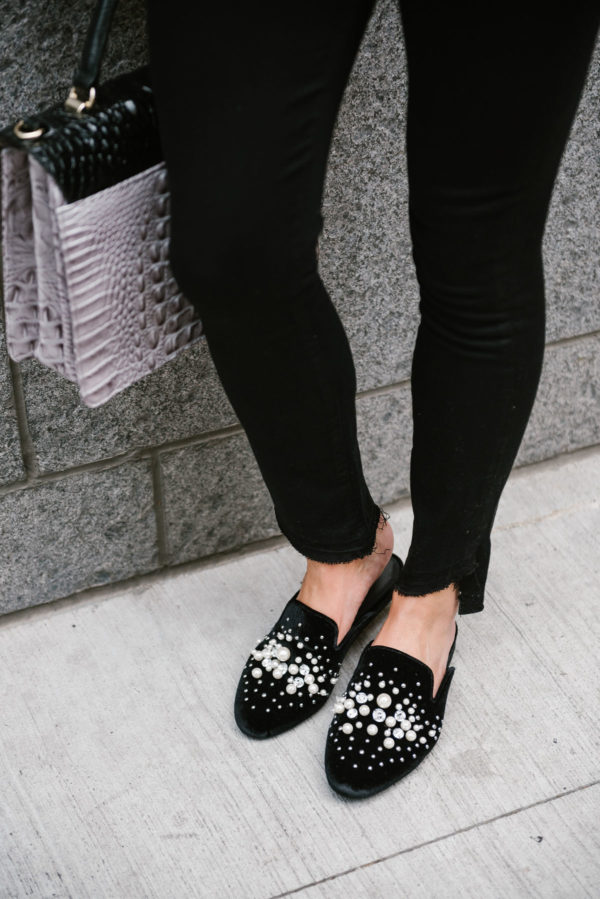 Bows & Sequins wearing raw hem black denim and black Steve Madden pearl slides.