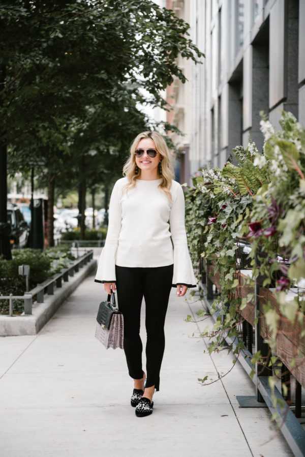 Chicago fashion and lifestyle blogger Bows & Sequins wearing a white Halogen bell sleeve sweater, black Paige jeans, Steve Madden pearl slides, Gucci aviators, and a Brahmin handbag.