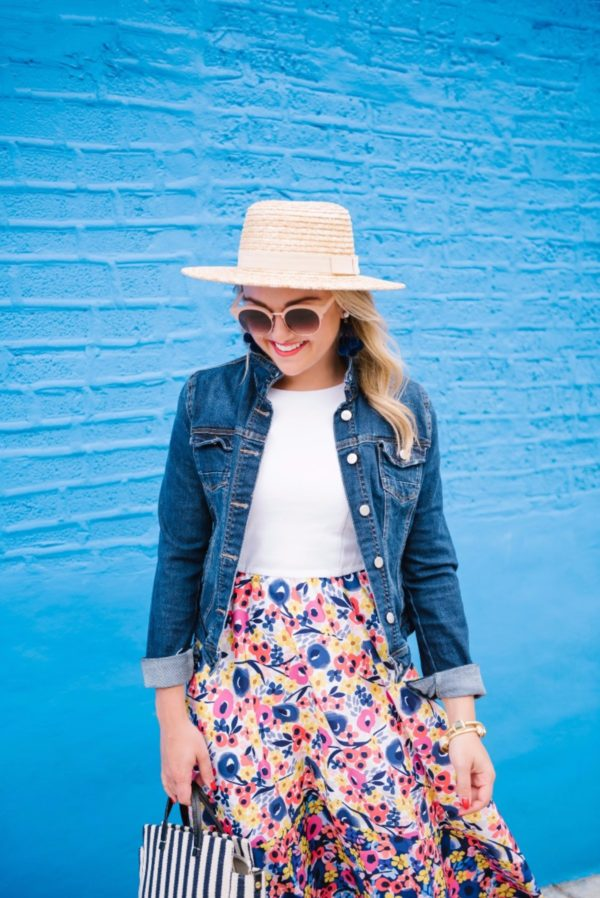 Chicago fashion blogger Bows & Sequins wearing a L Space straw hat and a floral Hutch dress from Anthropologie with a dark wash denim jacket, BaubleBar pom pom earrings, Nordstrom earrings, and a Clare V stripe tote.