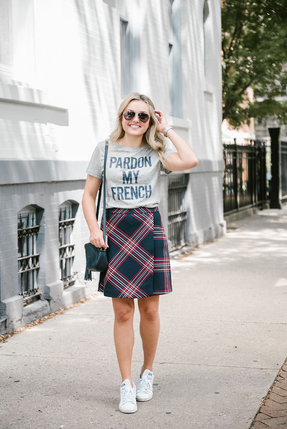 Bows & Sequins wearing a Pardon My French tee from J.Crew with a plaid skirt and Stan Smith sneakers.