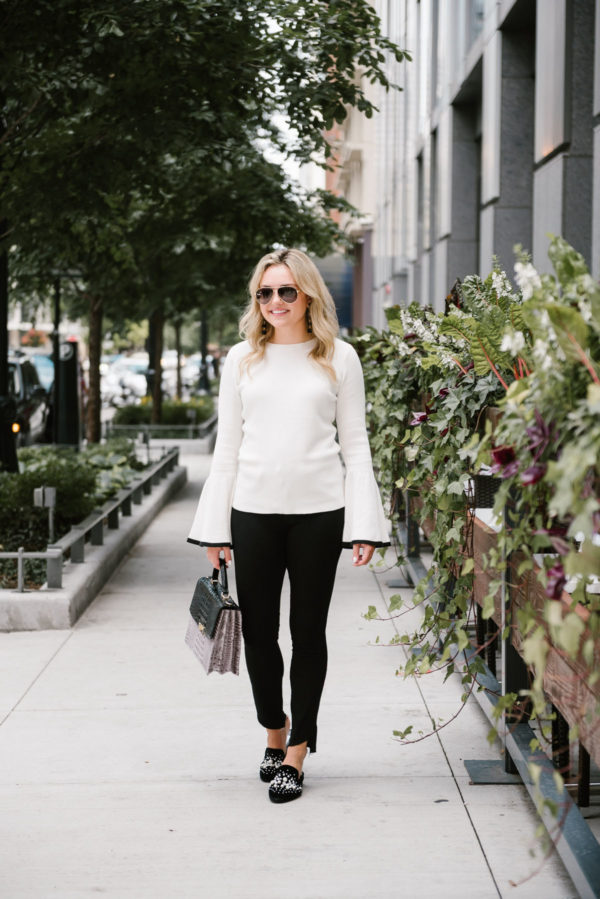 Bows & Sequins wearing a white Halogen bell sleeve sweater, raw hem Paige black denim, and Steve Madden pearl slides.