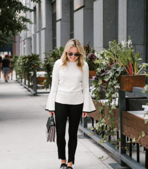 Chicago blogger Bows & Sequins wearing a black & white outfit from the Nordstrom Anniversary Sale: a flare sleeve Halogen sweater, black Paige jeans, and embellished pearl slides with a Brahmin handbag and Gucci aviators.
