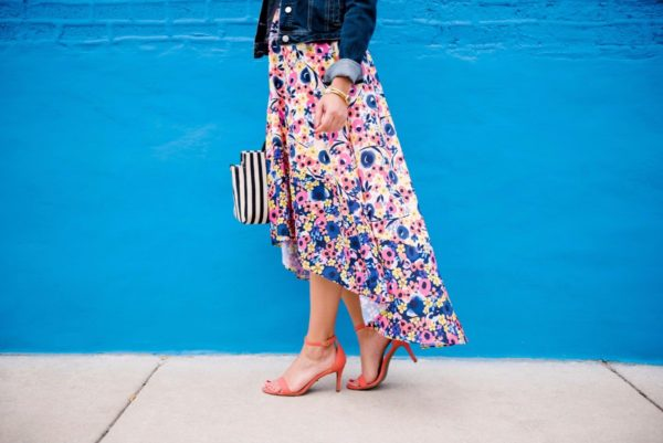 Chicago lifestyle blogger Bows & Sequins wearing a floral high-low dress from Anthropologie with coral ankle strap heels from Old Navy with a Clare V striped tote and a denim jacket.