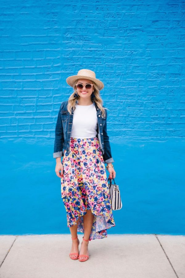 Bows & Sequins wearing a high-low floral dress with coral heels and a straw hat.