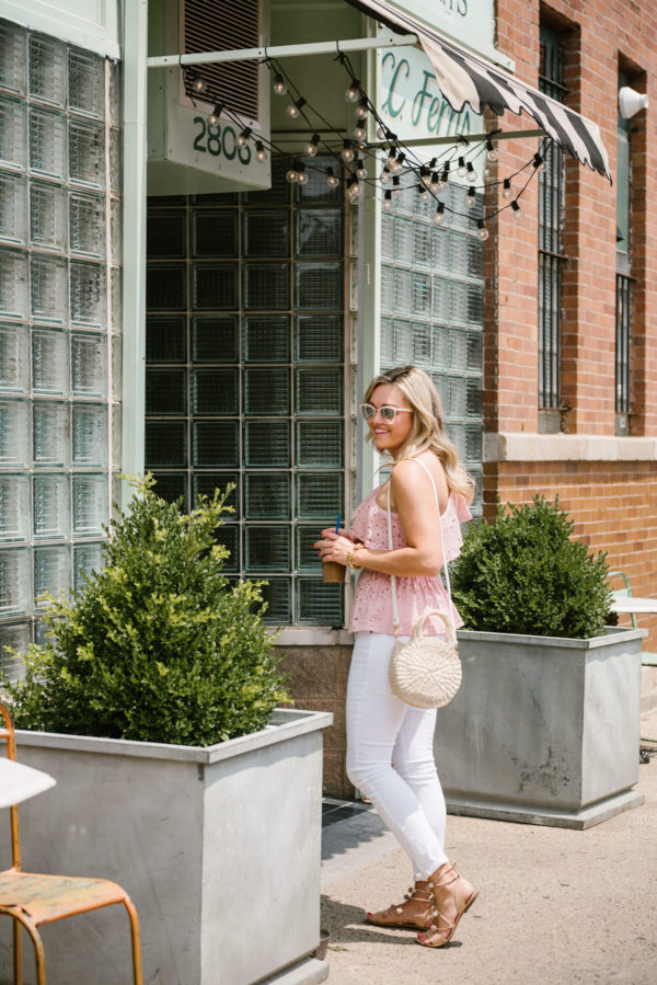 Chicago fashion blogger Bows & Sequins wearing an eyelet peplum top with white denim, blush pink sunglasses, pom pom sandals, and a straw tote.