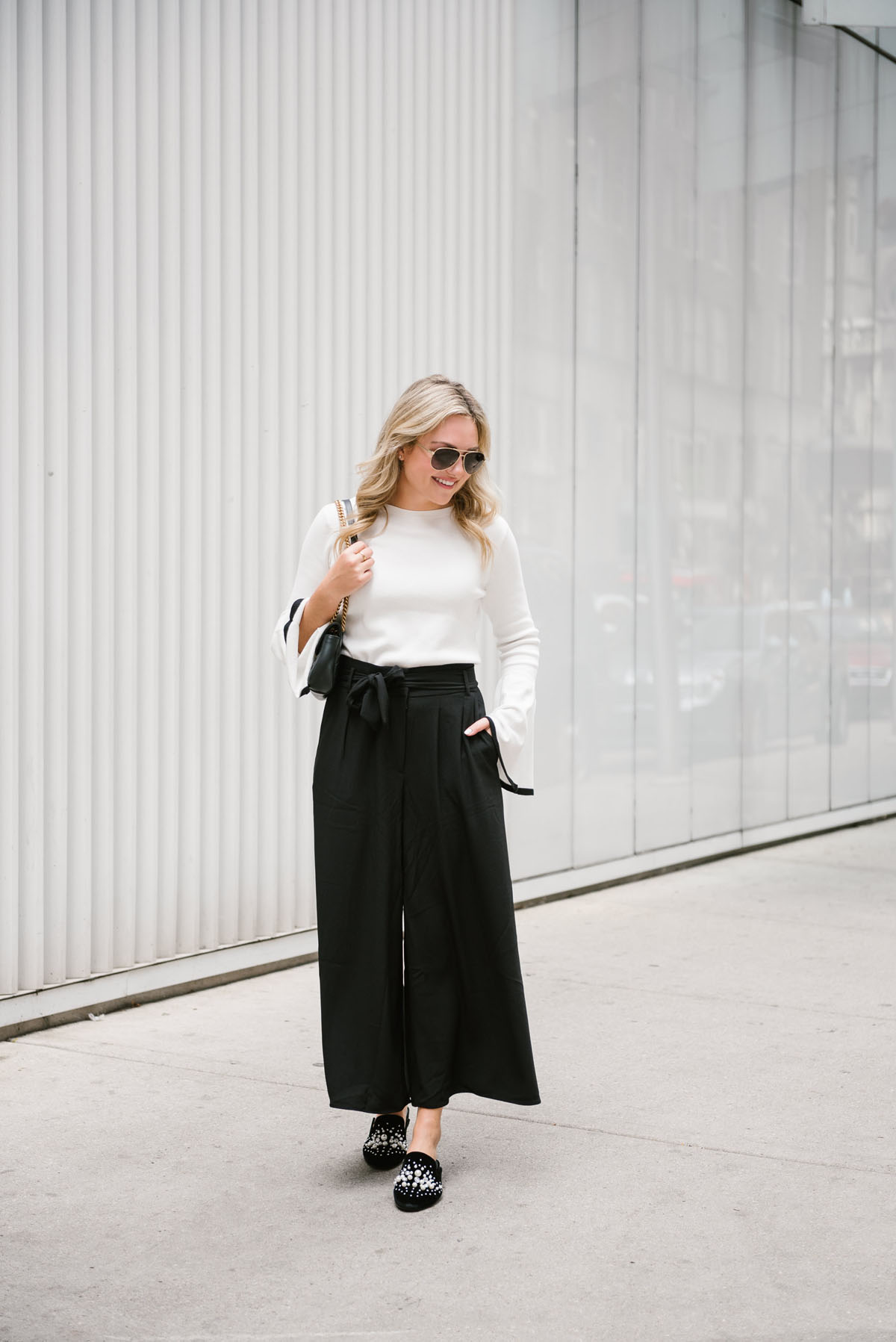 Fashion blogger Bows & Sequins wearing a black and white work wear outfit with a Gucci bag and aviators.