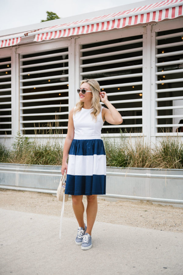 Fashion and lifestyle blogger Bows & Sequins wearing a navy and white striped dress with a Clare V straw bag and Coach aviators in Chicago.