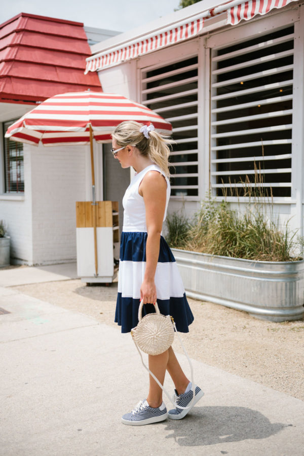 Bows & Sequins, a fashion-focused lifestyle blogger, wearing a navy and white summer dress with a natural straw handbag and navy gingham sneakers in Chicago.