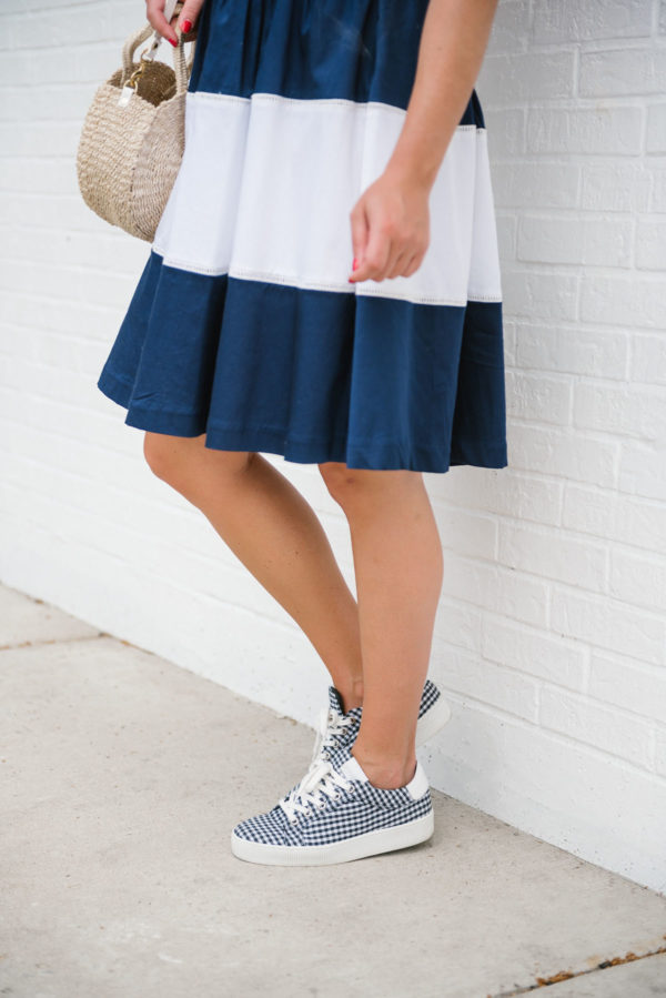Bows & Sequins wearing a navy and white striped dress with gingham Claudie Pierlot sneakers and a Clare V straw bag.