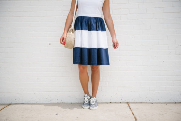 Fashion blogger Bows & Sequins wearing a navy and white striped dress with gingham Claudie Pierlot sneakers and a Clare V straw bag in Chicago.